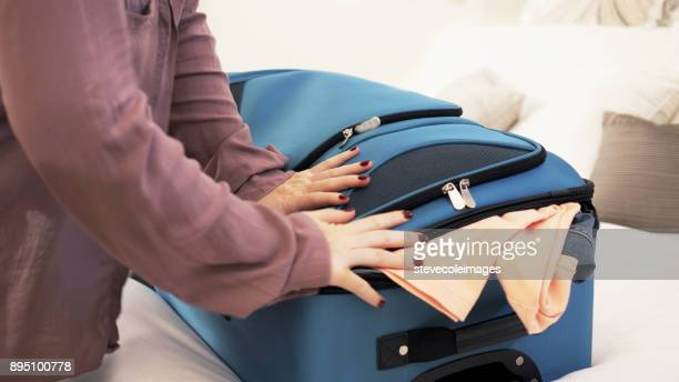 Woman packing overfilled suitcase.