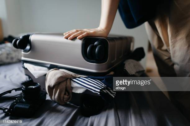 woman packing suitcase for holiday and struggling with overflowing suitcase on the bed at home - packing stock pictures, royalty-free photos & images