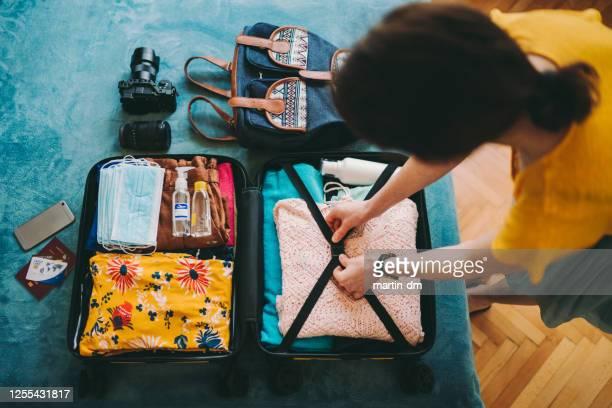 donna imballaggio valigia per viaggio - valigia foto e immagini stock