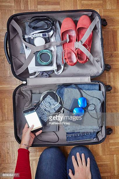 Woman packing suitcase, holding smartphone, overhead view
