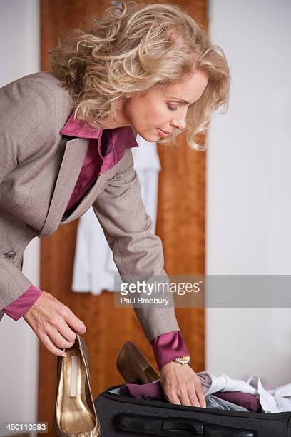 woman packing suitcase - alleen één oudere vrouw stockfoto's en -beelden