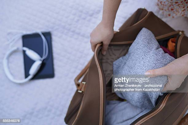 woman packing travel bag on a bed - chiuso per ferie foto e immagini stock