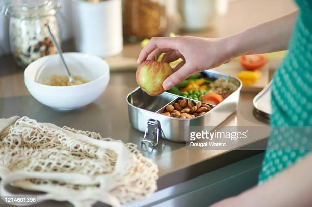 woman packing vegan food into plastic free lunchbox at home. - lunch bag stock pictures, royalty-free photos & images