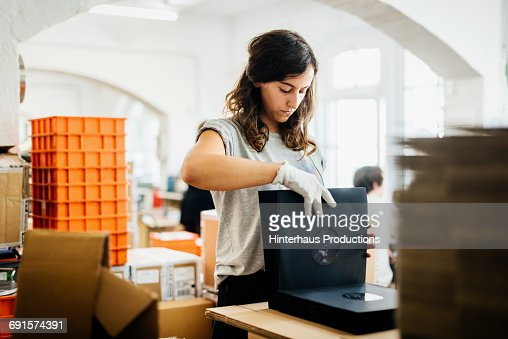 Woman packing vinyl records in sleeves