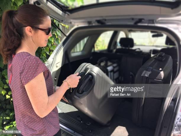 woman packing/unpacking suitcases from a car boot - rafael ben ari fotografías e imágenes de stock