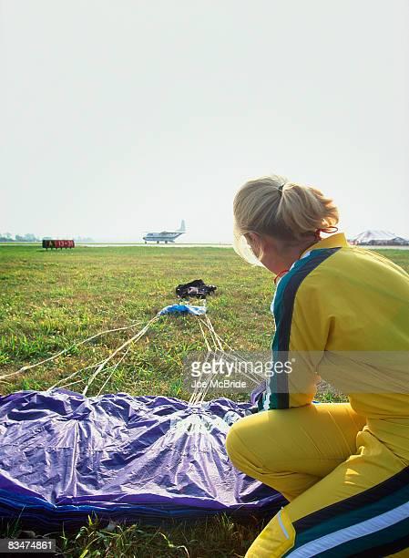 woman packs parachute in runway vacinity. - fallschirm stock-fotos und bilder