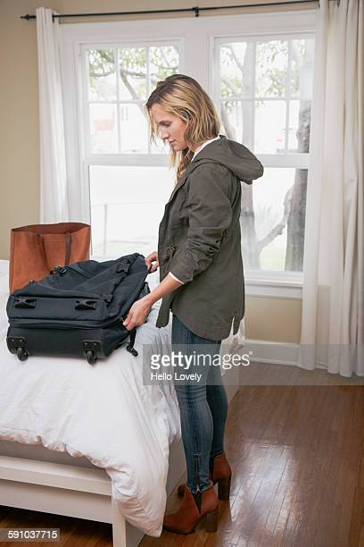 Woman packs suitcase