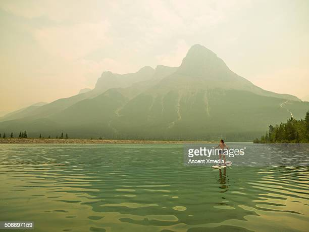 woman paddle boarder navigates mountain lake - paddling stock pictures, royalty-free photos & images