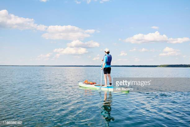 woman paddle boarding (sup) on lake müritz, mecklenburg-vorpommern, germany - mecklenburg vorpommern stock pictures, royalty-free photos & images