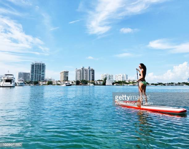 woman paddleboarding on sea against blue sky - miami beach stock pictures, royalty-free photos & images