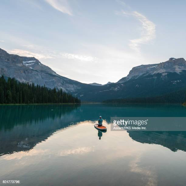 Woman paddleboards across mountain lake, sitting down