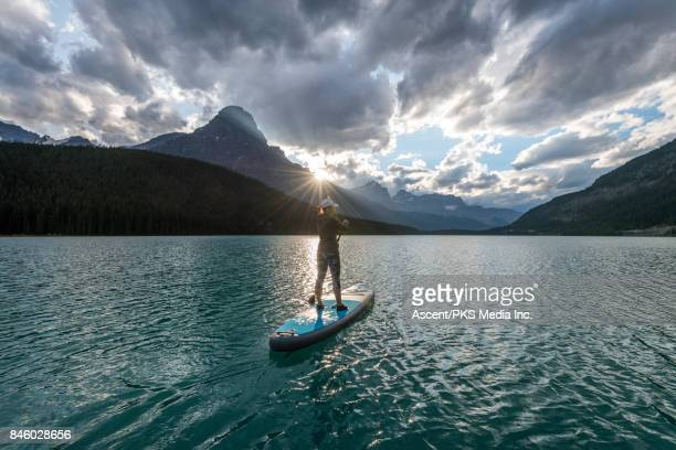Woman paddleboards across mountain lake, standing up