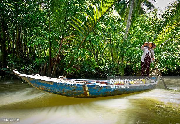 Woman paddles a boat along one of the thousands of Mekong tributaries in Can Tho Province, Southern Vietnam.