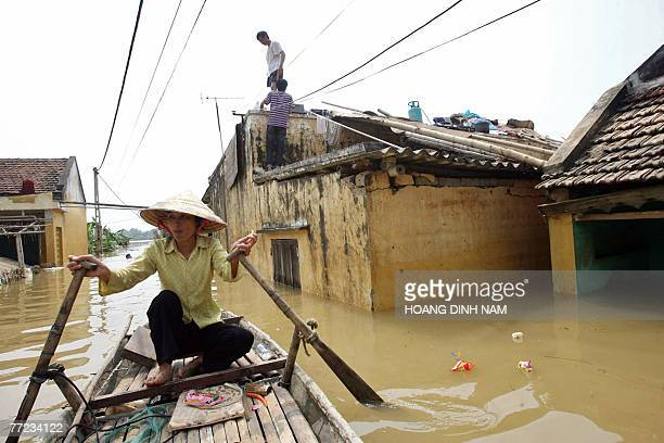 A woman paddles a raft on a flooded street in Thach Thanh district in the central province of Thanh Hoa 08 October 2007 At least 58 people have died...