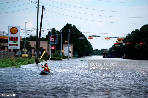 Woman paddles down a flooded road while shuttling deliveries for her neighbors during the aftermath of Hurricane Harvey on August 30, 2017 in...