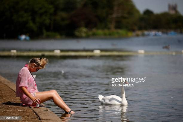 Woman paddles her feet in Serpentine lake in the sunshine in Hyde Park in London on June 14, 2021. - Britain was on Monday widely expected to delay...