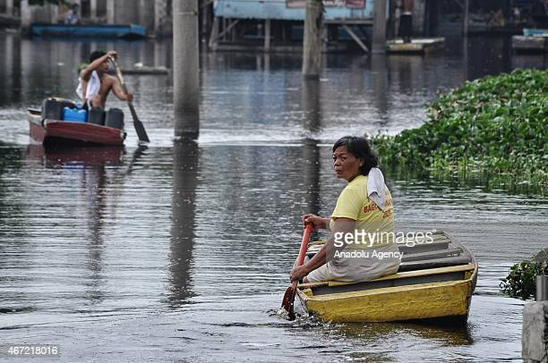 A woman paddles inside the submerged residential compund at Artex in Malabon City North of Manila on Sunday Today marks the celebration of the World...