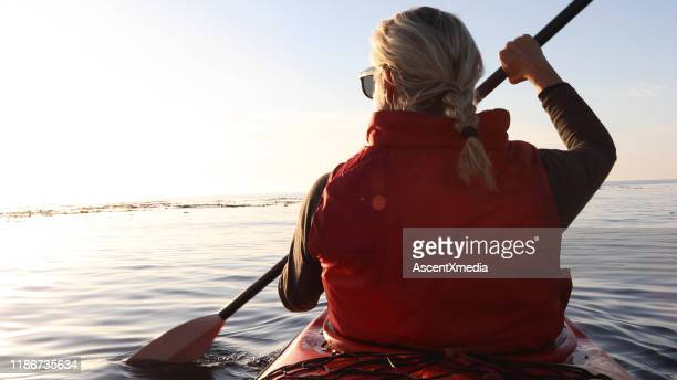woman paddles kayak at sunrise - early retirement stock pictures, royalty-free photos & images