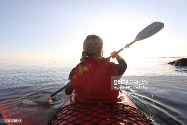 Woman paddles kayak on calm sea, towards sunrise