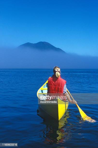 woman paddles yellow canoe solo on the ocean - paddling stock pictures, royalty-free photos & images