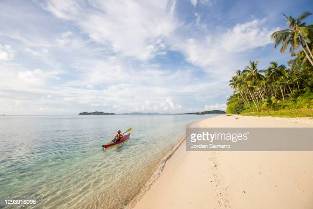a woman paddling a canoe through the turquoise water of the philippines. - capital region stock pictures, royalty-free photos & images