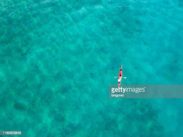 woman paddling a kayak from above - kayak foto e immagini stock