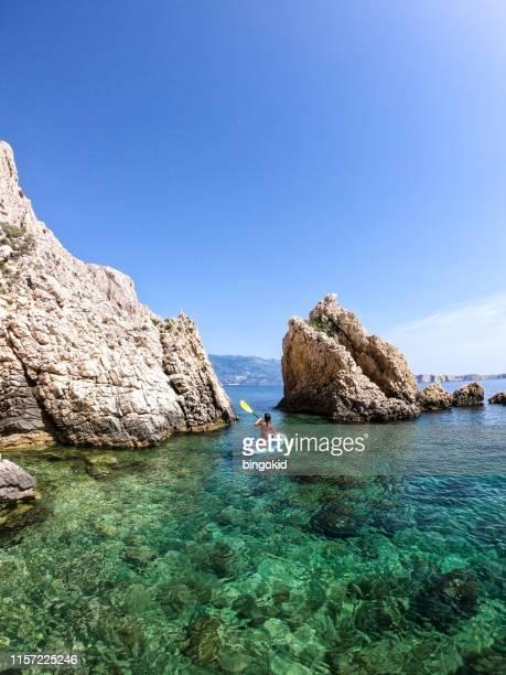 mujer remando entre rocas - croacia fotografías e imágenes de stock