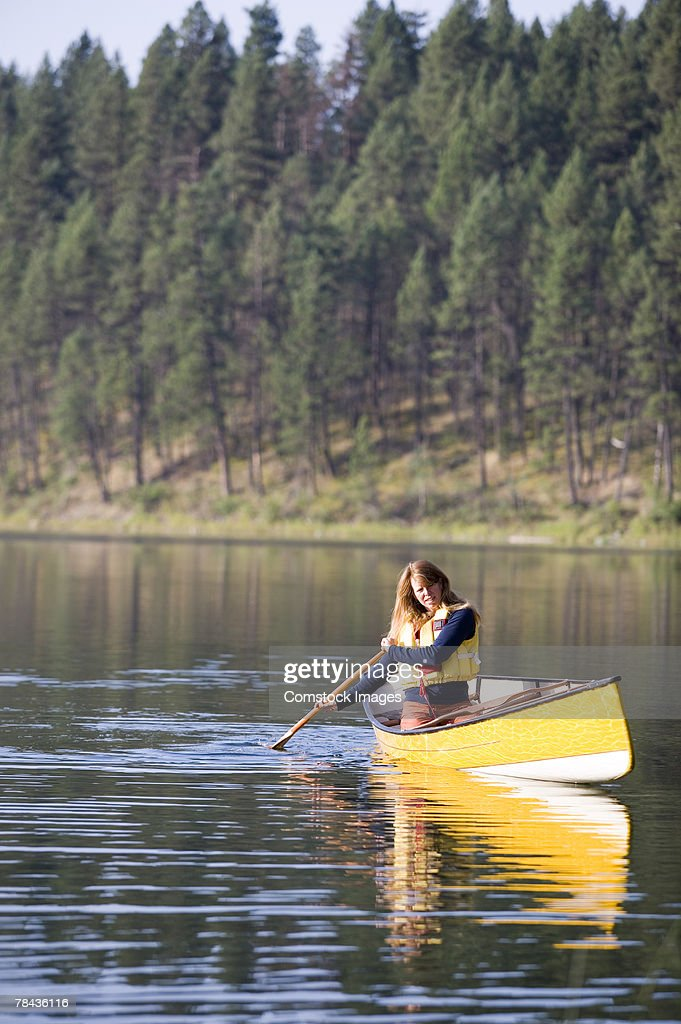 Woman paddling canoe : Stockfoto