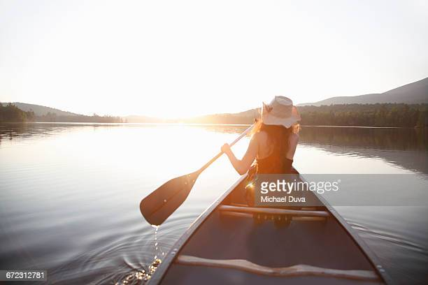 woman paddling into sunset on a lake in a canoe