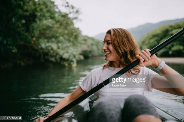 woman paddling kayak in mangrove river, iriomote island, japan - スポーツ  ストックフォトと画像