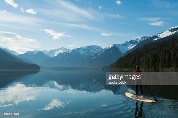woman paddling on a stunning mountain lake - whistler british columbia stock pictures, royalty-free photos & images