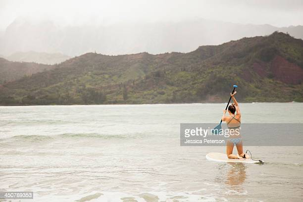 Woman paddling on shallow water