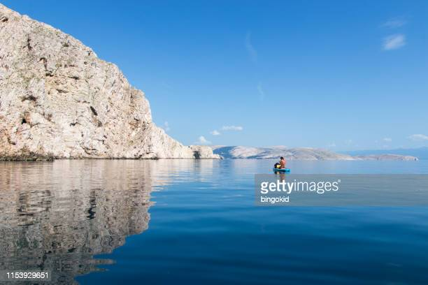woman paddling over calm glassy sea - adriatic sea stock pictures, royalty-free photos & images
