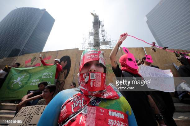 A woman painted and wearing plastic labels takes part in a demonstration as part of the Global Climate Strike on September 20 2019 in Mexico City...