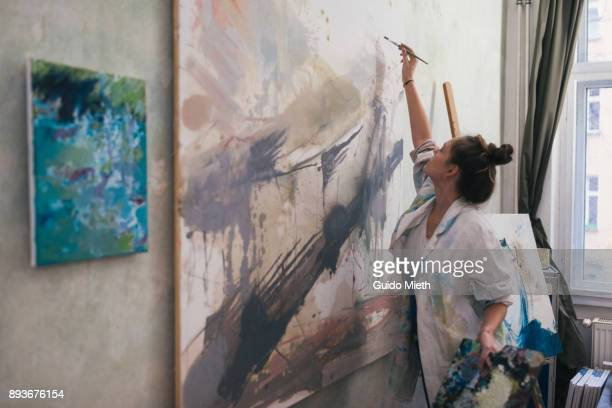 woman painting a big work in studio. - dipinto foto e immagini stock