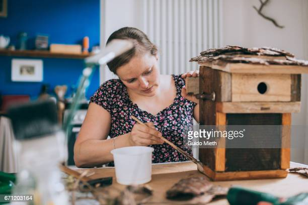 Woman painting a bird house.