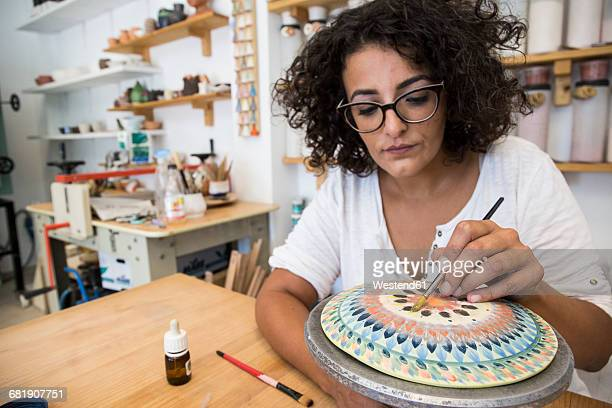 woman painting a ceramic plate with a brush - pottery stock pictures, royalty-free photos & images