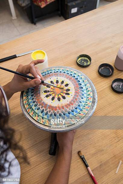 Woman painting a ceramic plate with a brush