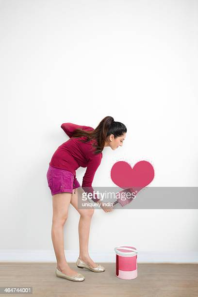 Woman painting a heart shape on a wall
