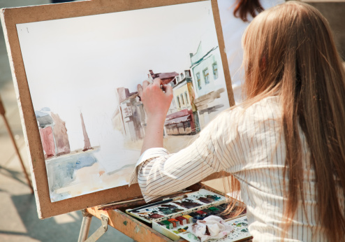Woman painting a portrait of a city street in watercolors 94144862