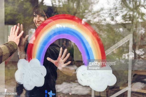 woman painting a rainbow on a window - thank you stock pictures, royalty-free photos & images