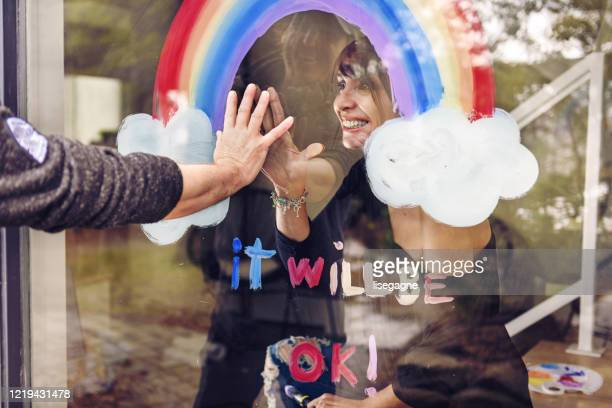 woman painting a rainbow on a window - photographed through window stock pictures, royalty-free photos & images