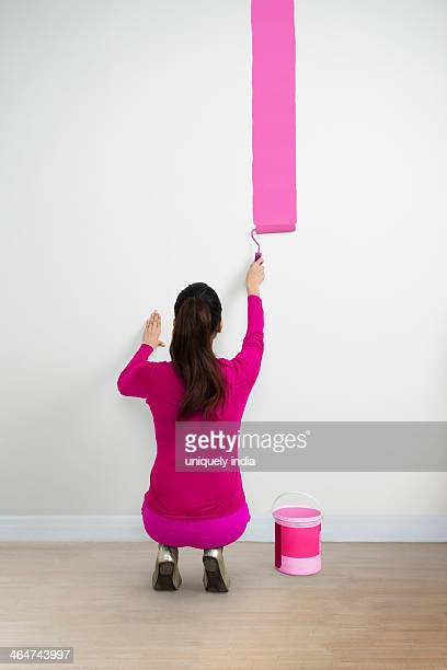 Woman painting a wall with a pink color
