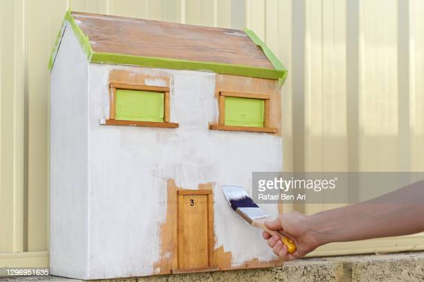 woman painting an old wooden dolls house - ドールハウス ストックフォトと画像