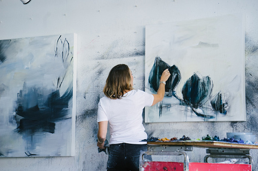 Woman painting canvas in art studio 1050437632
