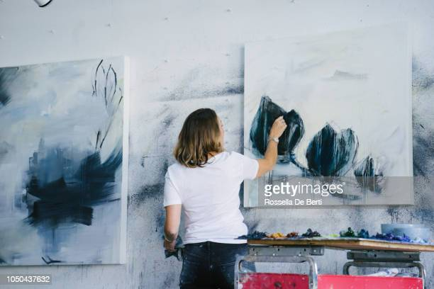 woman painting canvas in art studio - dipinto foto e immagini stock