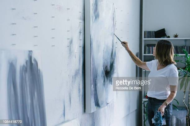 Woman painting canvas in art studio