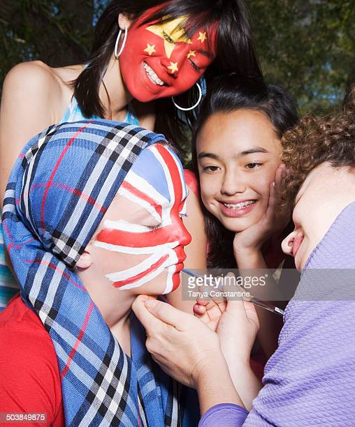 Woman painting Chinese and United Kingdom flags on children's faces