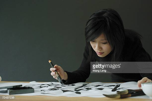Woman painting Chinese calligraphy