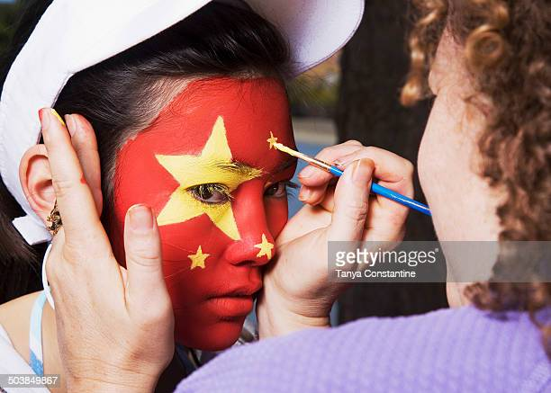 Woman painting Chinese flag on Chinese girl's face